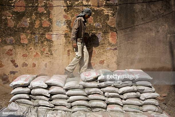 An Indian laborer stamps on a pile of cement bags at a building site in Gurgaon India on Wednesday Oct 3 2007 ACC Ltd India's biggest cementmaker by...