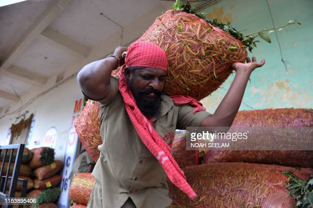 An Indian labourer carries a sack of green chillies at a vegetable wholesale market in Hyderabad on July 5 2019 India's newly reelected government...
