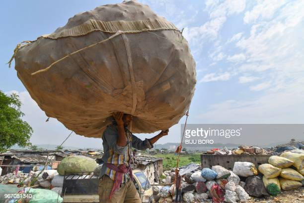 TOPSHOT An Indian labourer carries a sack of plastic bottles on his head near one of the largest disposal sites in northeast India ahead of the...