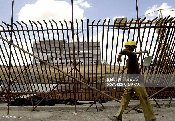 An Indian labourer carries a shovel as he walks in front of construction for a Prototype Fast Breeder Reactor at the Indira Gandhi Centre for Atomic...