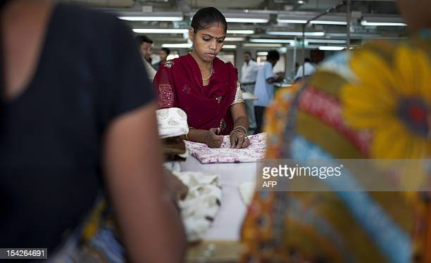 An Indian labourer cuts loose strings at the April Cornell clothing factory in Noida on the outskirts of New Delhi on October 16 2012 The April...