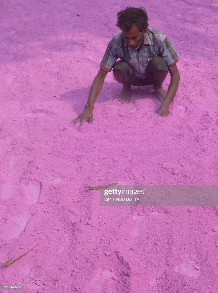 An Indian labourer dries coloured powder to be used during the forthcoming spring festival of Holi, at a factory in Fulbari village, on the outskirts of Siliguri on February 21, 2018. Holi, the popular Hindu spring festival of colours is observed in India at the end of the winter season on the last full moon of the lunar month, and will be celebrated on March 2 this year. /