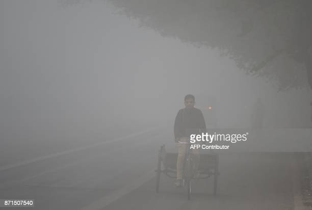 An Indian labourer drives a rickshaw amid heavy smog in New Delhi on November 8 2017 Delhi shut all primary schools on November 8 as pollution levels...