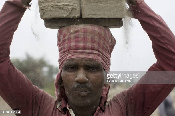 An Indian labourer loads clay bricks on his head before taking them to a brick kiln in Farakka in the Indian state of West Bengal on April 3 2019 /...