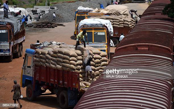 An Indian labourer loads grain sakcs on to a truck at a railway goods yard in Chennai on August 3 2016 Finance Minister Arun Jaitley said India was...