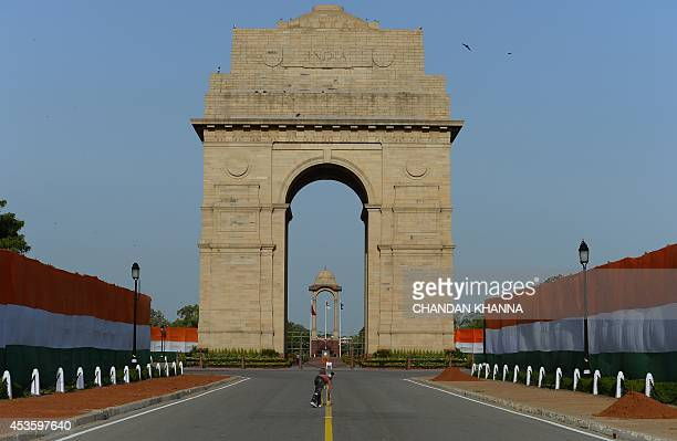 An Indian labourer paints a road divider line at India Gate in New Delhi on August 14 on the eve of Independence Day India celebrates its anniversary...