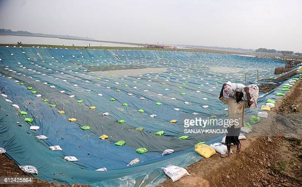 An Indian labourer prepares a temporary pond using plastic sheeting into which idols of the Hindu Goddess Durga will be immersed after Durga Puja as...
