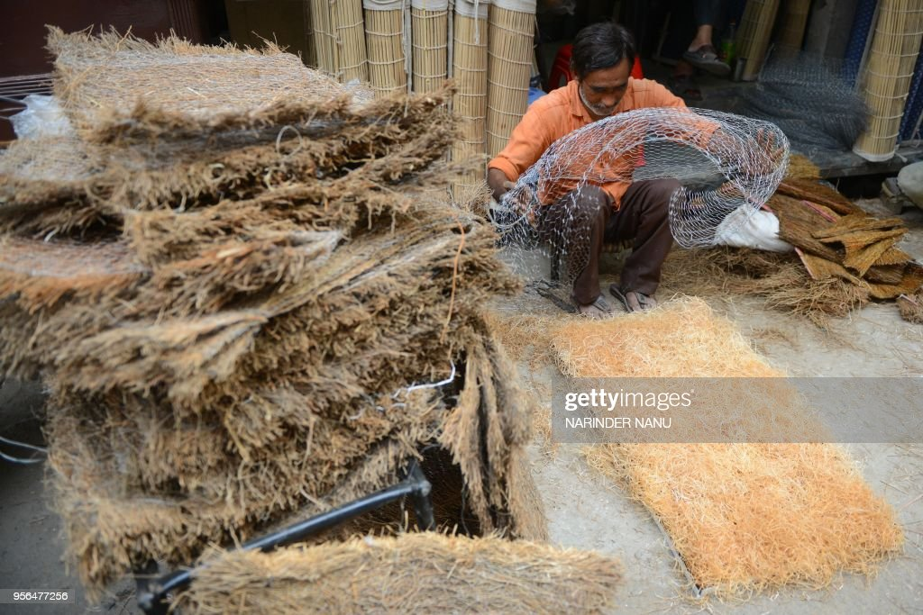 An Indian labourer prepares handmade air cooler pads at the roadside in Amritsar on May 92018