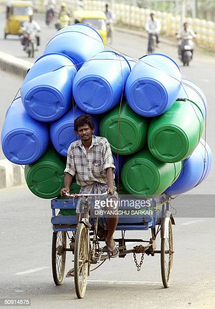 An Indian labourer rides his rickshaw laden with plastic water containers along a street in Madras 01 June 2004 Traders dealing in water containers...