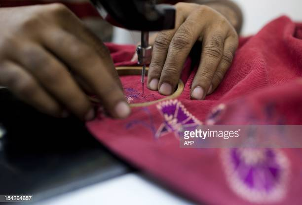 An Indian labourer sews patterns at the April Cornell clothing factory in Noida on the outskirts of New Delhi on October 16 2012 The April Cornell...
