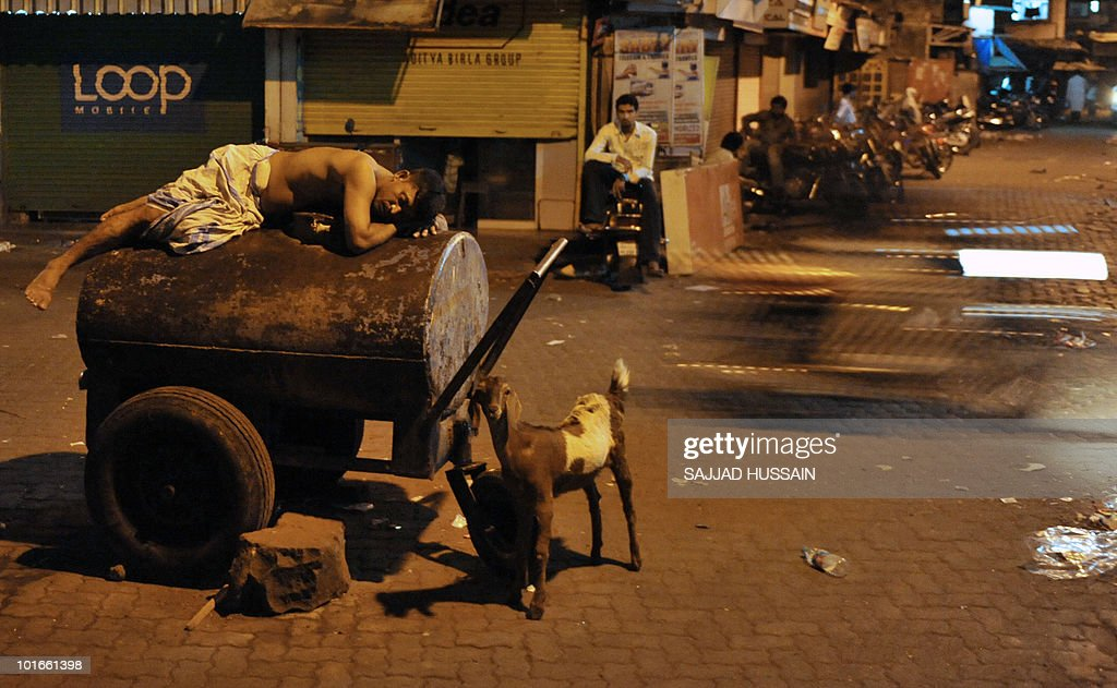 An Indian labourer sleeps on a water tank in Mumbai on May 15, 2010. Many low-income Indians spend the hot summer nights sleeping outdoors as they seek respite from the soaring temperatures. AFP PHOTO/ Sajjad HUSSAIN