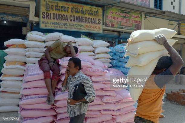 An Indian labourer takes a nap on piled up sacks of food grain at the APMC wholesale trading market in Bangalore on February 28 2017 India's economic...