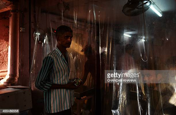 An Indian labourer waits outside a shop at a spice market in the old quarters of New Delhi on September 15 2014 The labour sector of the Indian...