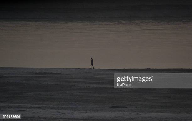 An indian labourer walks on the banks of Ganeges river as he works out during preperation of Annual Magh mela, in Allahabad on December...