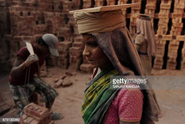 TOPSHOT An Indian labourer works at a brick factory near Allahabad on April 30 on the eve of International Labour Day / AFP PHOTO / Sanjay KANOJIA