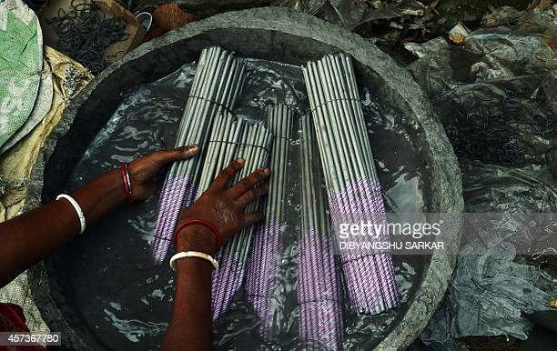 An Indian labourer works at a firecracker factory on the outskirts of Kolkata on October 17 2014 Hindu devotees use firecrackers while celebrating...
