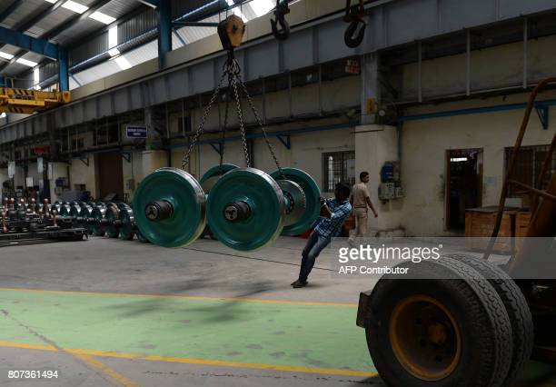 An Indian labourer works to build an Indian Railways locomotive coach at Integral Coach Factory in Chennai on July 4 2017 / AFP PHOTO / ARUN SANKAR