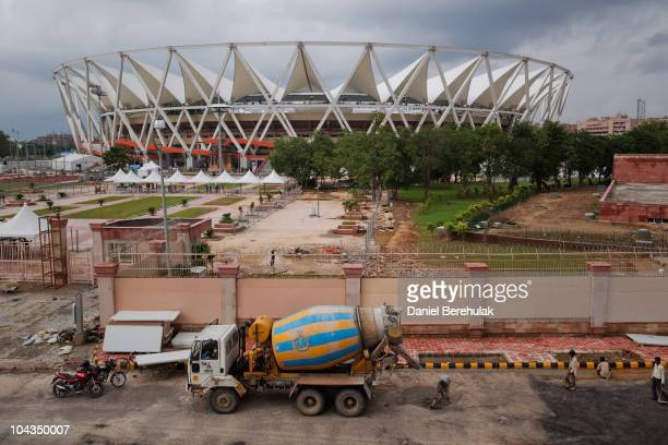 An Indian labourers work outside of the main stadium for the approaching 19th Commonwealth Games 2010 Delhi at Jawaharlal Nehru Stadium on September...