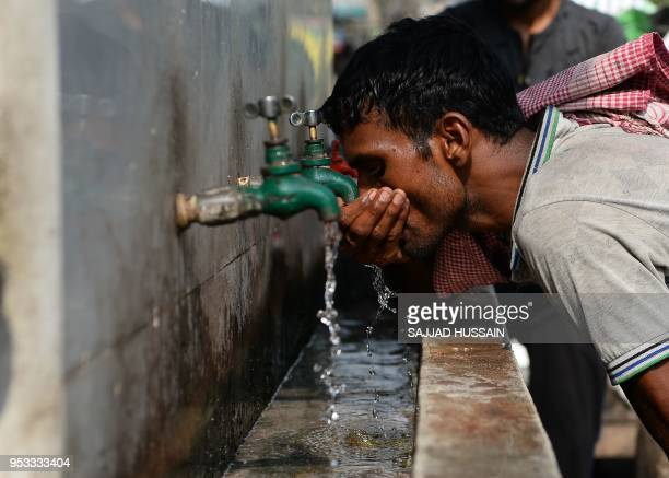 An Indian labrourer drinks water at a public water fountain on a hot summer day in the old quarters of New Delhi on May 1, 2018.