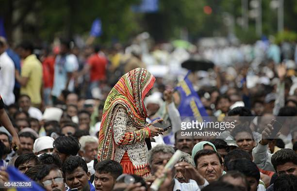An Indian lady and a supporter of Dalit caste community plays functions on her mobile phone as she crosses during a protest rally against an earlier...