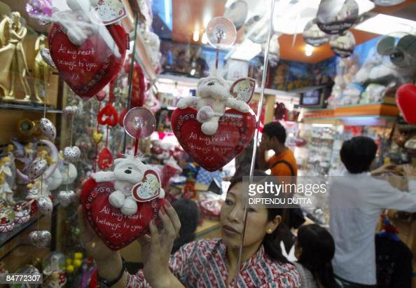 An Indian lady arranges gift items in a gift shop in