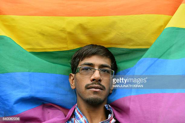 An Indian LGBT activist holds a flag during a demonstration and candlelight vigil held in Bangalore on June 14 condemning the killing of 49 people in...