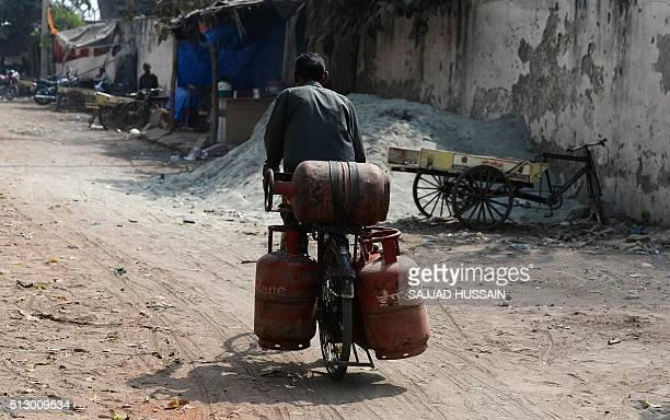 An Indian Liquid Petroleum Gas vendor carries gas cylinders on a cycle outside a depot in New Delhi on February 29 2016 In his budget statement...