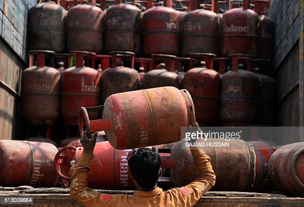 An Indian Liquid Petroleum Gas vendor loads empty gas cylinders onto a truck outside a depot in New Delhi on February 29 2016 In his budget statement...