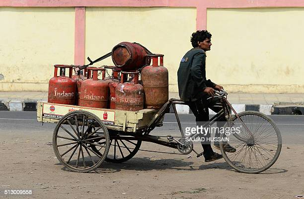 An Indian Liquid Petroleum Gas vendor sits on a cycle rickshaw laden with gas cylinders outside a depot in New Delhi on February 29 2016 In his...
