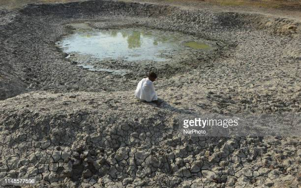 An indian local man takes rest on parched area of shrunken Varuna River during a hot day, in Phoolpur , some 45 kms from Allahabad on June 8, 2019....