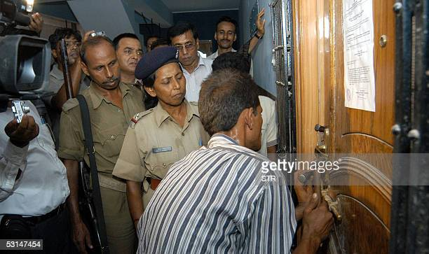 An Indian locksmith is watched by policemen and bystanders as he attempts to forcibly open the door of an apartment owned by Gautam Goswami in Patna...
