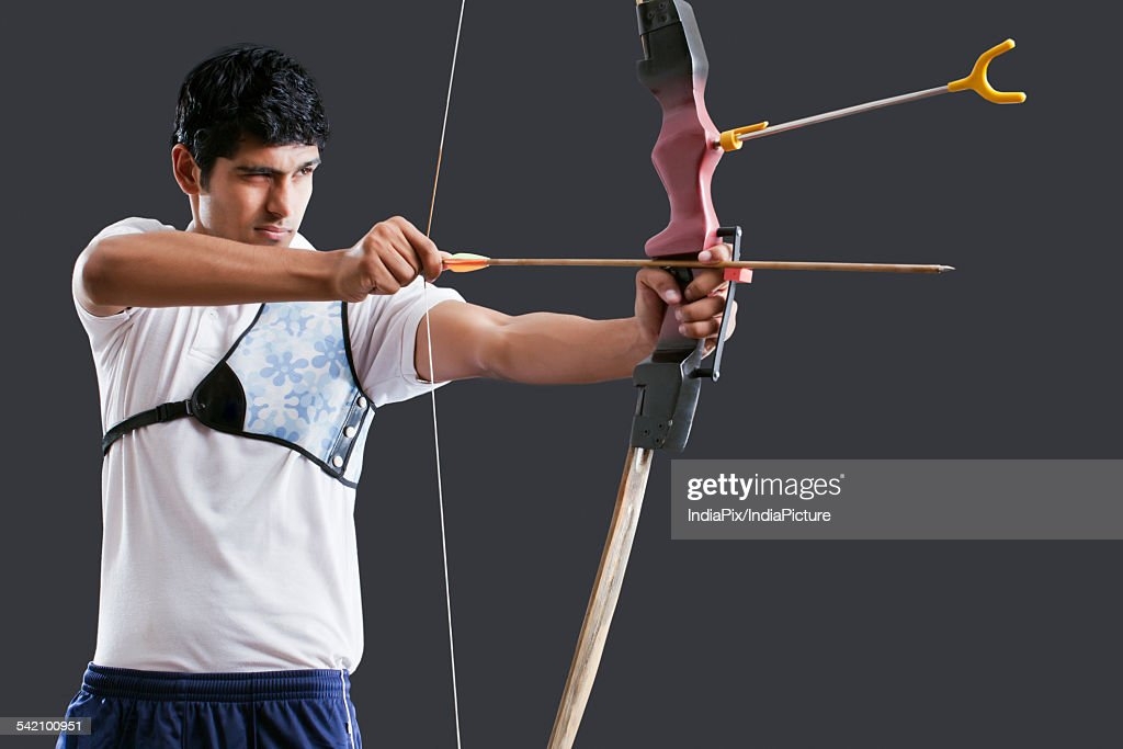 An Indian male archer aiming over black background : Stock Photo