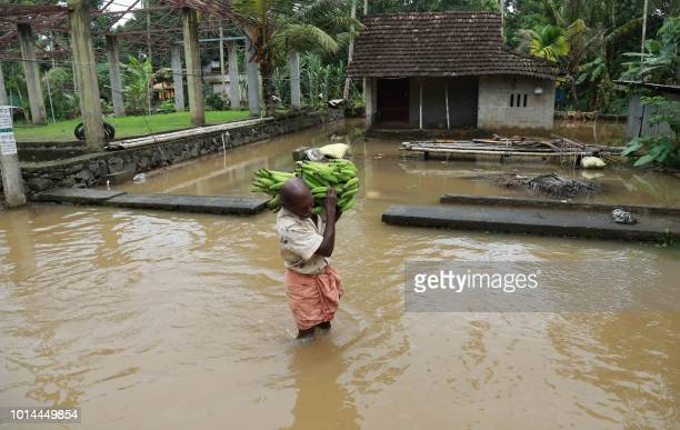 An Indian man carries a basket of bananas next to houses immersed in flood waters in Ernakulam district of Kochi in the Indian state of Kerala on...