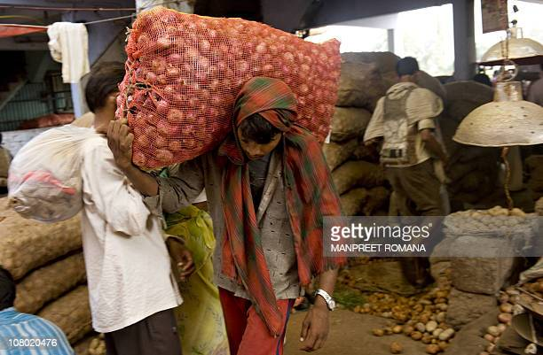 An Indian man carries a sack of onions at a vegetable market in New Delhi on October 1, 2009. Indian inflation accelerated sharply as the weakest...