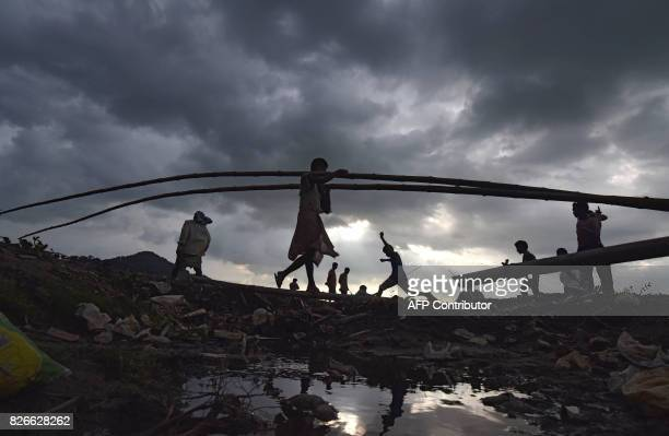 TOPSHOT An Indian man carries bamboo at a bamboo market at the banks of the river Brahmaputra in Guwahati the capital city of Indias northeastern...