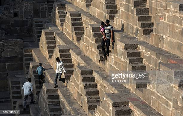 An Indian man carries his child down the steps of the historic Chand Baori stepwell in Abhaneri village of western Rajasthan state on September 24...