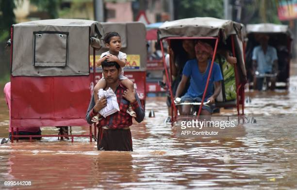 An Indian man carries his son as he walks through a flooded street after heavy rain in Guwahati on June 22 2017 / AFP PHOTO / Biju BORO