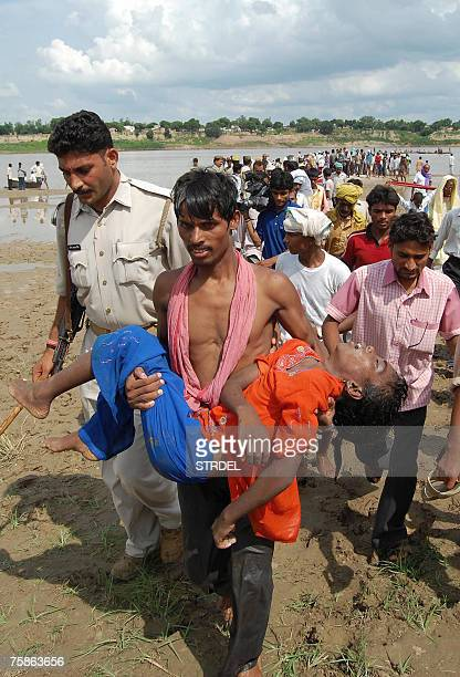 An Indian man carries the body of a child after a boat capsized on the River Ganges at Garwa Ghat some 15 kms from Varanasi 30 July 2007 One person...