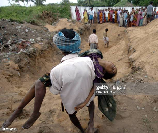 An Indian man carries the dead body of a girl to a mass burial site at Silver Beach in Cuddalore,some 185 kms south of Madras, 27 December 2004,...