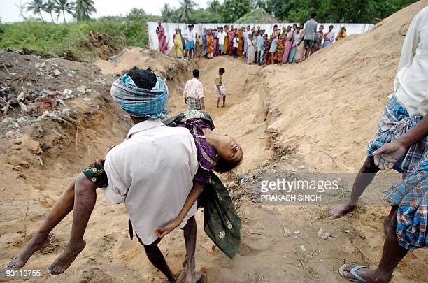 An Indian man carries the dead body of a girl to a mass burial site at Silver Beach in Cuddalore some 185 kms south of Madras 27 December 2004 after...