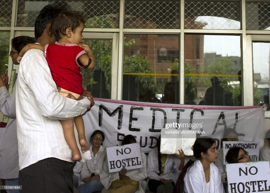 An Indian man carrying his child walks past junior doctors taking part in a protest at Safdarjung Hospital in New Delhi on June 2, 2010. Over 500 junior doctors, including postgraduate students, interns and junior residents of Delhi's Safdarjung Hospital went on a mass hunger strike on June 1 to protest against the 'lack of basic services',also threatening to boycott Out Patient Department (OPD) services.