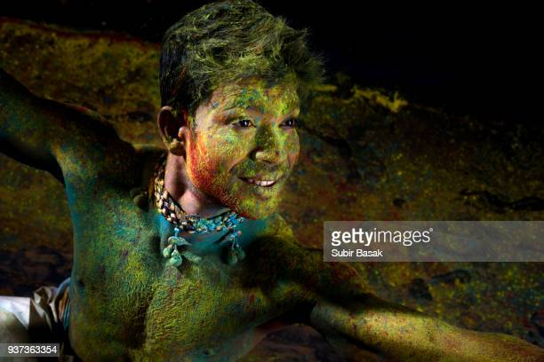 An Indian man celebrating Holi with colors.