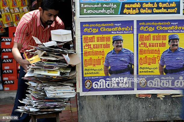 An Indian man collects scrap paper near posters of slain Liberation Tigers of Tamil Eelam leader Velupillai Prabhakaran in Mumbai on May 26 2009 Sri...