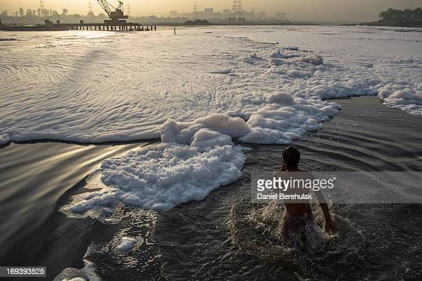 An Indian man collects water as he bathes in an industrial wastefoam polluted section of the Yamuna River on the outskirts of New Delhi on May 24...