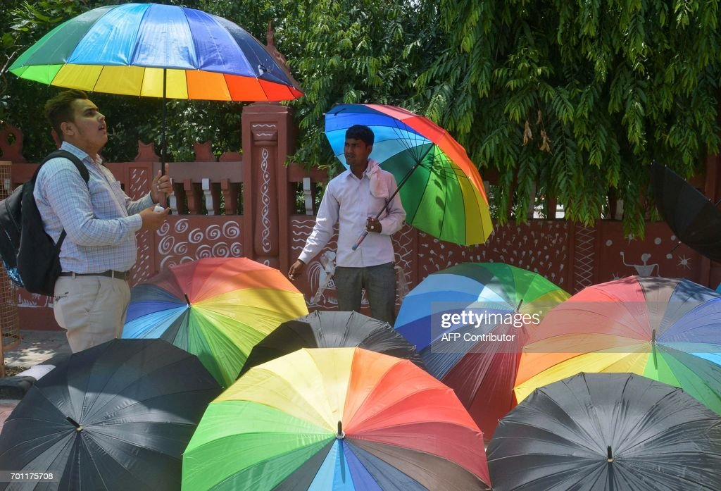 An Indian man considers buying an umbrella as a vendor looks on in Amritsar on June 22 ahead of the rainy monsoon season / AFP PHOTO / NARINDER NANU