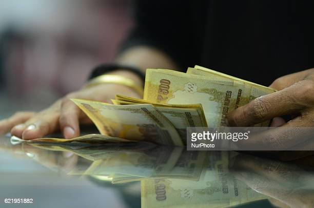 An indian man counts his 500 rupee notes at railway ticket counter in Allahabad on November 92016 Indian Prime Minister Narendra Modi announced...