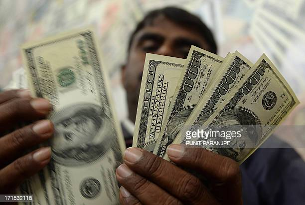 An Indian man counts US dollar notes as he poses for a picture at the local currency exchange shop in Mumbai on June 26 2013 India's rupee touched a...