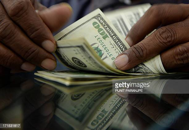 An Indian man counts US dollar notes at a local currency exchange shop in Mumbai on June 26 2013 India's rupee touched a record low of more than 60...