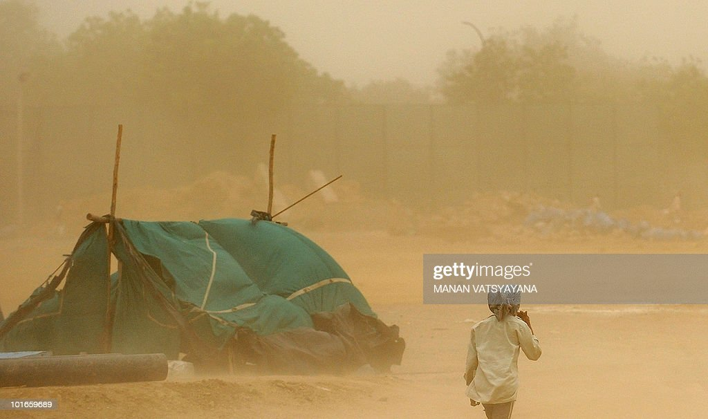 An Indian man covers his face during a dust storm in New Delhi on June 6, 2010. Northern India has been suffering from record high temperatures in a deadly heatwave which has reportedly caused 156 deaths.