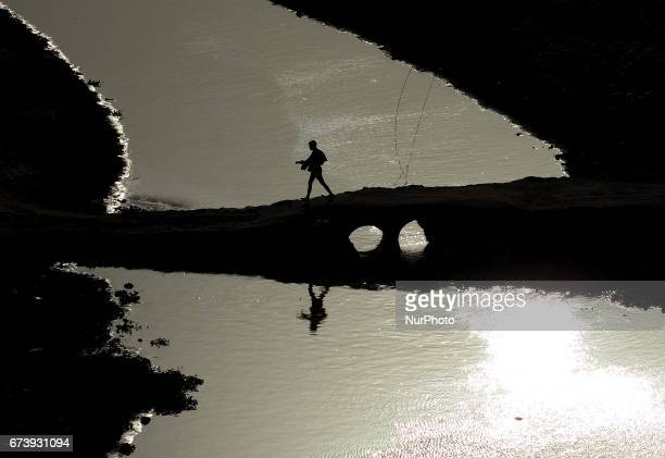 An indian man crosses dried Ganges river through a temporary bridge during a hot day in Allahabad on April 272017 In the third and forth week of...